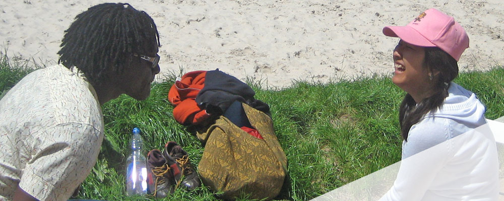 Internationale Jugendliche unterhalten sich am Rand des Beachvolleyballfeldes