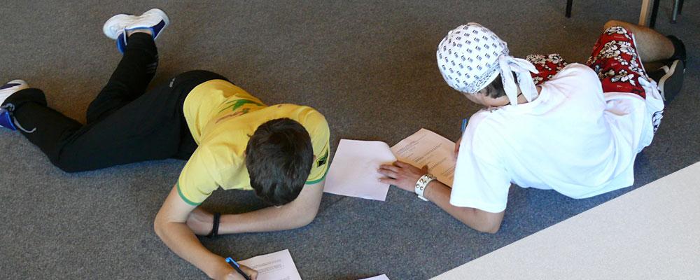Zwei Jugendliche bearbeiten eine Aufgabe