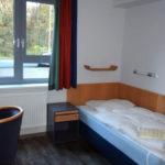 Helles Einzelzimmer mit Bett und Tisch